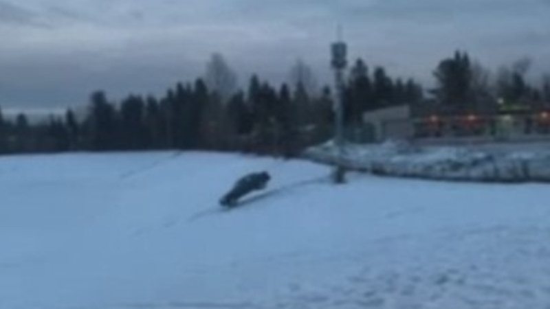 "A car lands on a snowy hill at College Heights Secondary School in Prince George, B.C. during what police have called a ""dangerous stunt."" (Facebook)"