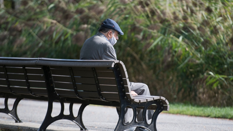 An elderly man wears a face mask as he sits in a city park in Montreal, Sunday, October 4, 2020, as the COVID-19 pandemic continues in Canada and around the world. THE CANADIAN PRESS/Graham Hughes