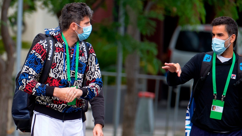 Italian tennis player Simone Bolelli, left, and Argentina's Maximo Gonzalez are escorted to their training session in Melbourne, Australia, Monday, Jan. 18, 2021. (Luis Ascui/AAP Image via AP)