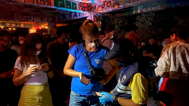 In this Tuesday, Jan. 26, 2021 photo, a Thai immigration officer talks to people at a bar on Koh Phangan island, Surat Thani province, southern Thailand. (Police Investigation Team of Surat Thani Immigration via AP)