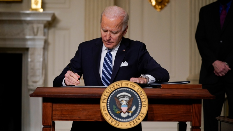 U.S. President Joe Biden signs an executive order on climate change, in the State Dining Room of the White House, Wednesday, Jan. 27, 2021, in Washington. (AP Photo/Evan Vucci)