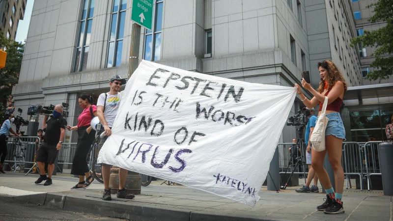 "Multimedia artist Katelyn Kopenhaver, right, with help from her brother Brent Kopenhaver, unfurls a banner reading ""[Jefferey] Epstein is the worst kind of virus,"" outside federal court where a judge held a bail hearing by video for Epstein's former girlfriend Ghislaine Maxwell, Tuesday, July 14, 2020, in New York. (AP Photo/Bebeto Matthews)"