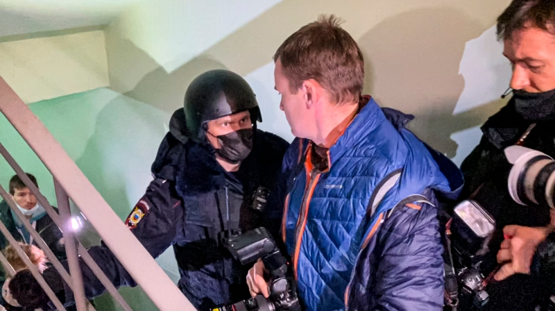 A police officer pushes photographers from a door of the apartment where Oleg Navalny, brother of jailed opposition leader Alexei Navalny lives in Moscow, Russia, Wednesday, Jan. 27, 2021. (AP Photo/Mstyslav Chernov)