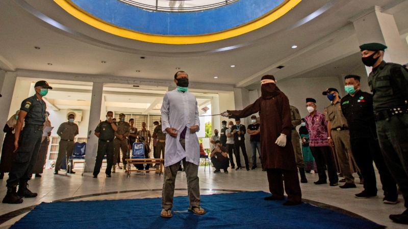 A Shariah Law official uses a rattan cane to whip one of two men convicted of gay sex in Banda Aceh, Aceh province, Indonesia, on Jan. 28, 2021. (Riska Munawarah / AP)