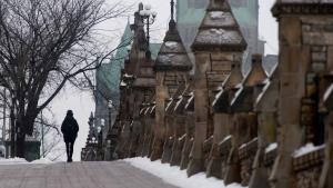 A person walks along the sidewalk near Parliament Hill, on Jan. 14, 2021. (Adrian Wyld / THE CANADIAN PRESS)