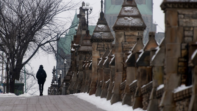 A person walks along the sidewalk near Parliament Hill, on Jan. 14, 2021. (Adrian Wyld / THE CANADIAN PRESS)