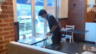 File image of a restaurant employee in Calgary cleaning a table during the pandemic.