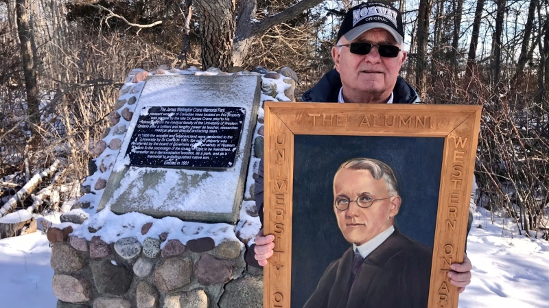 Jim Crane holds a portrait of his uncle, Dr. James Crane in front of a cairn in Dr. Crane's memory at the site of a wooded area he donated for conservation in Elgin County, Ont., Tuesday, Feb. 2, 2021. (Sean Irvine / CTV News)