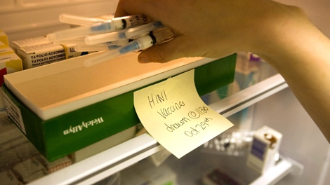 A registered nurse stores prepared syringes of H1N1 flu vaccine in a fridge at a Toronto health clinic on Thursday, Oct. 29, 2009. (Darren Calabrese / THE CANADIAN PRESS)