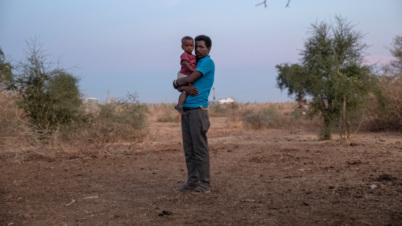 A Tigray man holds his son in the Umm Rakouba refugee camp. in Qadarif, eastern Sudan, Monday, Dec. 14, 2020. (AP Photo/Nariman El-Mofty)