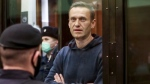 In this handout photo taken from a footage provided by Moscow City Court, Russian opposition leader Alexei Navalny stands in the cage during a hearing to a motion from the Russian prison service to convert the suspended sentence of Navalny from the 2014 criminal conviction into a real prison term in the Moscow City Court in Moscow, Russia, Tuesday, Feb. 2, 2021.  (Moscow City Court via AP)