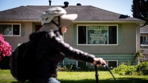 A woman rides a bicycle past a house with the message 'Thank you for fighting COVID-19' hung in the window, in Vancouver, Monday, May 18, 2020. (THE CANADIAN PRESS / Darryl Dyck)