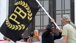 In this Sept. 7, 2020 photo, a protester carries a Proud Boys banner, symbol of a right-wing group, while other members start to unfurl a large U.S. flag in front of the Oregon State Capitol in Salem, Ore. (AP / Andrew Selsky, File)