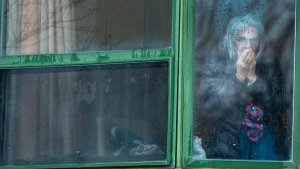A resident looks out her window from the Herron seniors residence Monday April 13, 2020 in Dorval near Montreal's Trudeau airport. Thirty -one residents are confirmed to have died in the past month.THE CANADIAN PRESS/Ryan Remiorz
