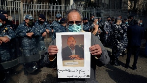 An anti-Hezbollah protester holds a picture of Lokman Slim during a protest in front of the Justice Palace in Beirut, Lebanon, on Feb. 4, 2021. (Bilal Hussein / AP)