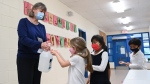 FILE - Children sanitize their hands while physical distancing after getting their pictures taken at picture day at St. Barnabas Catholic School during the COVID-19 pandemic in Scarborough, Ont., on Tuesday, October 27, 2020. THE CANADIAN PRESS/Nathan Denette