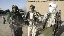 Taliban militants stand beside burnt trucks, background left, on main Ghazni- Kandahar highway in Ghazni, west of Kabul, on Monday, Oct.19, 2009. (AP / Rahmatullah Naikzad)