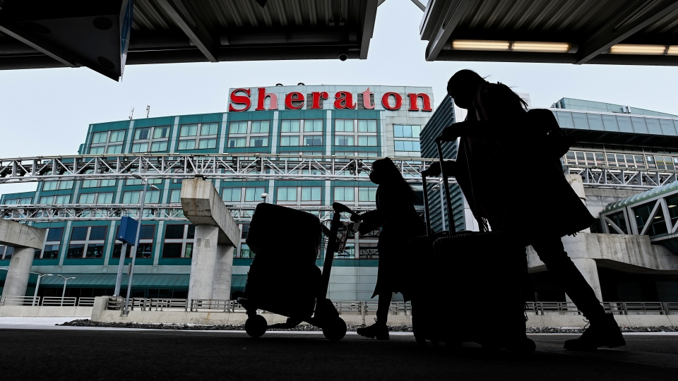The airport hotel is shown as people walk outside with their luggage at Pearson International Airport during the COVID-19 pandemic in Toronto on Tuesday, February 2, 2021. (THE CANADIAN PRESS/Nathan Denette)