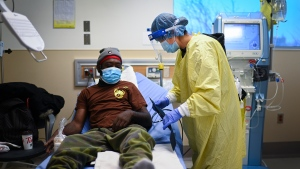 A health-care worker cares for Sterling Sam as he wears his protective mask while receiving dialysis at the Humber River Hospital during the COVID-19 pandemic in Toronto on Wednesday, December 9, 2020. THE CANADIAN PRESS/Nathan Denette