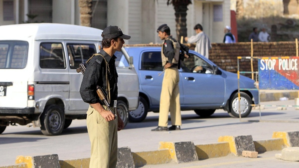 A police officer searches a car as another observes the area at a checkpoint in Peshawar, Pakistan, on Saturday, Oct. 31, 2009. (AP / Mohammad Sajjad)