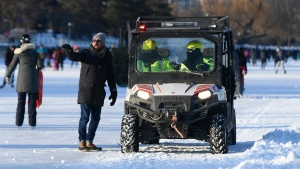 A person speaks to Ottawa Bylaw officers as they patrol the Rideau Canal Skateway in Ottawa, on the first weekend of Winterlude, Saturday, Feb. 6, 2021. Bylaw officers were present to enforce COVID-19 guidelines such as physical distancing. (Justin Tang/THE CANADIAN PRESS)