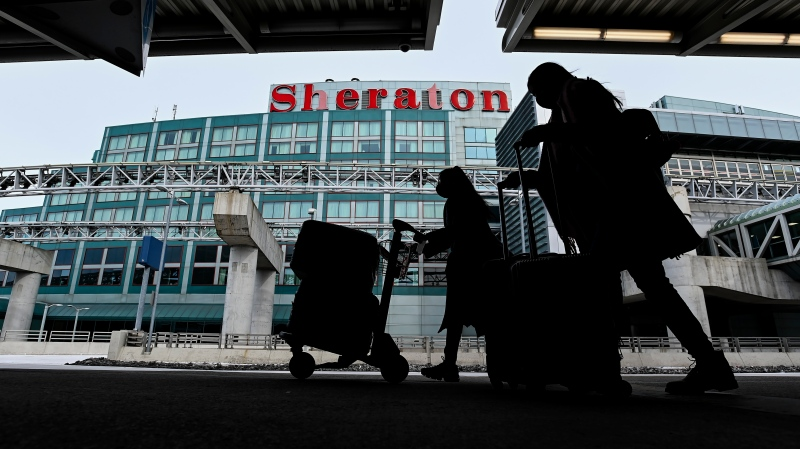 The airport hotel is shown as people walk outside with their luggage at Pearson International Airport during the COVID-19 pandemic in Toronto on Tuesday, February 2, 2021. THE CANADIAN PRESS/Nathan Denette