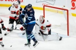 Winnipeg Jets' Pierre-Luc Dubois (13) screens Ottawa Senators goaltender Matt Murray (30) during second-period NHL action in Winnipeg on Thursday, February 11, 2021. THE CANADIAN PRESS/John Woods