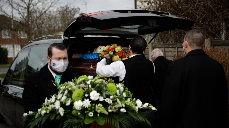 Staff from Heritage & Sons Funeral Directors in Aylesbury, southern England, arrange flowers after putting a coffin into a hearse ahead of the funeral service, Wednesday, Feb. 10, 2021. (AP Photo/Matt Dunham)