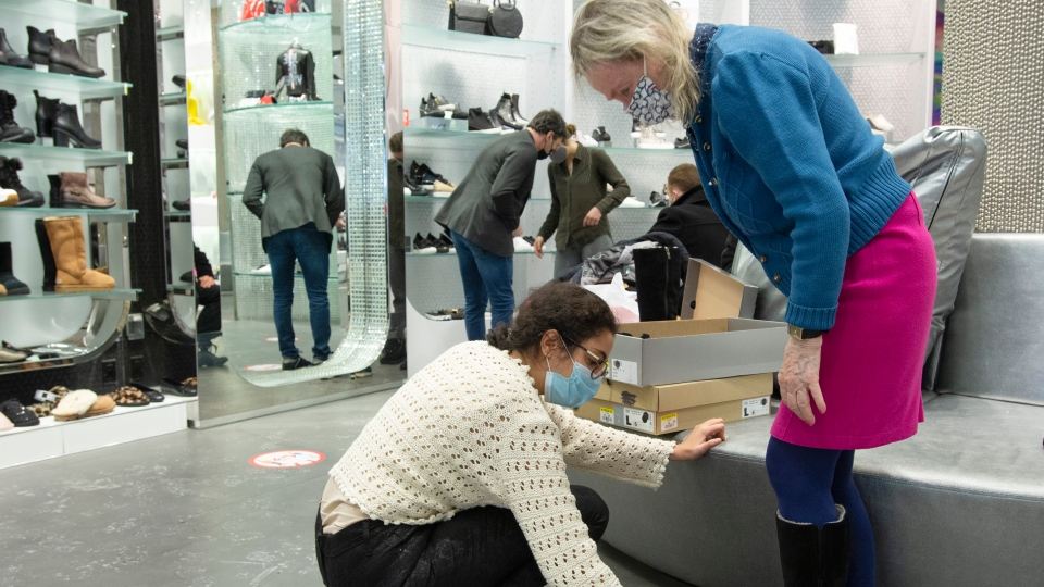 Customers shop for shoes as a slight easing of COVID-19 restrictions allow non-essential stores to reopen Monday, February 8, 2021 in Montreal.THE CANADIAN PRESS/Ryan Remiorz