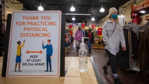 Erin Connolly wears a mask to protect them from the COVID-19 virus while looking at clothes at Trailhead in Kingston, Ontario, on Wednesday Feb. 10, 2021. Kingston, Frontenac and Lennox & Addington (KFL&A) Public Health unit has moved into the green zone. THE CANADIAN PRESS/Lars Hagberg