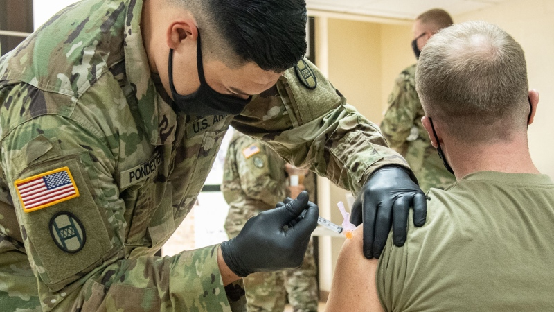 Members of the West Virginia National Guard conduct and participate in a COVID-19 vaccination clinic at Joint Forces Headquarters, Charleston, West Virginia, Jan. 13, 2021. (Edwin L. Wriston/US Army National Guard)
