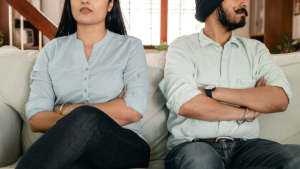 A couple sits on the couch with their arms crossed in this stock image. (Pexels/Ketut Subiyanto)