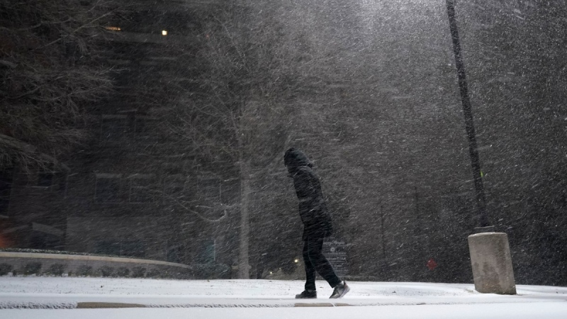 A woman walks through falling snow in San Antonio, Texas, on Feb. 14, 2021. (Eric Gay / AP)