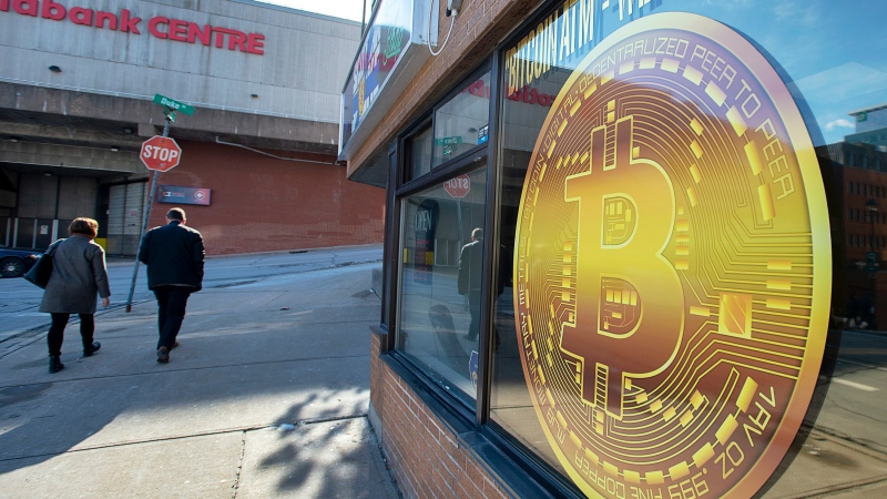 A sign advertises a Bitcoin automated teller machine, ATM, at a shop in Halifax on Wednesday, February 4, 2020. (THE CANADIAN PRESS/Andrew Vaughan)