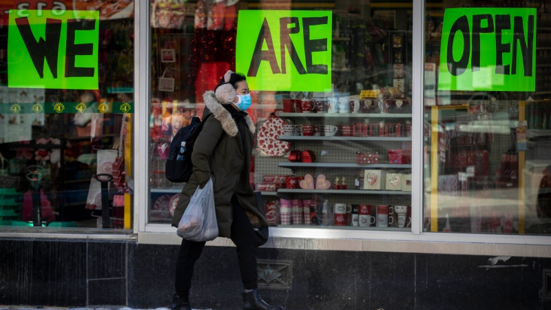 A person wears a mask to protect them from the COVID-19 virus while walking by an open store in Kingston, Ontario, on Wednesday Feb. 10, 2021. Kingston, Frontenac and Lennox & Addington (KFL&A) Public Health unit has moved into the green zone. THE CANADIAN PRESS/Lars Hagberg
