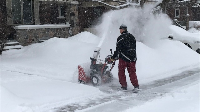A resident clears snow from his driveway in Wellington Village on Tuesday, Feb. 16, 2021. (Jim O'Grady/CTV News Ottawa)