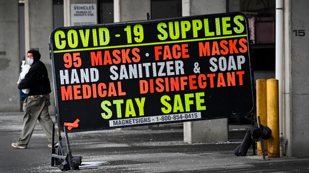 A man walks past a COVID-19 retail supplies sign during the COVID-19 pandemic in Toronto on Friday, February 5, 2021. THE CANADIAN PRESS/Nathan Denette