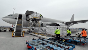 Boxes containing vaccines are unloaded from a Hungarian Airbus 330 cargo plane as the first batch of the vaccine against the new coronavirus produced by Sinopharm of China arrives at Budapest Liszt Ferenc International Airport in Budapest, Hungary, Tuesday, Feb. 16, 2021. (Zoltan Mathe/MTI via AP)