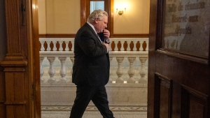 Ontario Premier Doug Ford walks past an open door as he arrives for the daily briefing in Toronto on Monday, February 8, 2021. THE CANADIAN PRESS/Frank Gunn