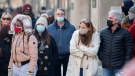 People wear face masks as they wait to cross a street in Montreal, Sunday, Feb. 14, 2021, as the COVID-19 pandemic continues in Canada and around the world. THE (CANADIAN PRESS/Graham Hughes)