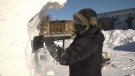Theressa Wright chips away at the 8 ft. snow block in City Centre Park in Yorkton. (Kaylyn Whibbs / CTV Yorkton)