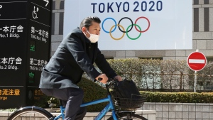 A man wearing a face mask cycles past the logo of the Tokyo Olympics, in Tokyo, Wednesday, Feb. 17, 2021. (AP Photo/Koji Sasahara)