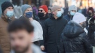 People wear face masks as they walk along a street in Montreal, Sunday, Feb. 14, 2021, as the COVID-19 pandemic continues in Canada and around the world. THE CANADIAN PRESS/Graham Hughes