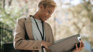 A woman looks at a binder in this stock image. (Pexels)