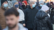 People wear face masks as they walk along a street in Montreal, Sunday, Feb. 14, 2021, as the COVID-19 pandemic continues in Canada and around the world. (THE CANADIAN PRESS/Graham Hughes)