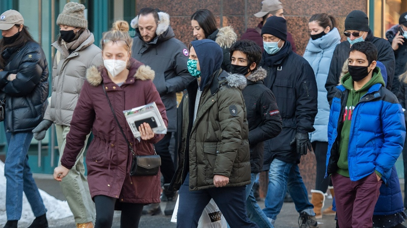 People wear face masks as they cross a street in Montreal, Sunday, Feb. 14, 2021, as the COVID-19 pandemic continues in Canada and around the world. THE CANADIAN PRESS/Graham Hughes