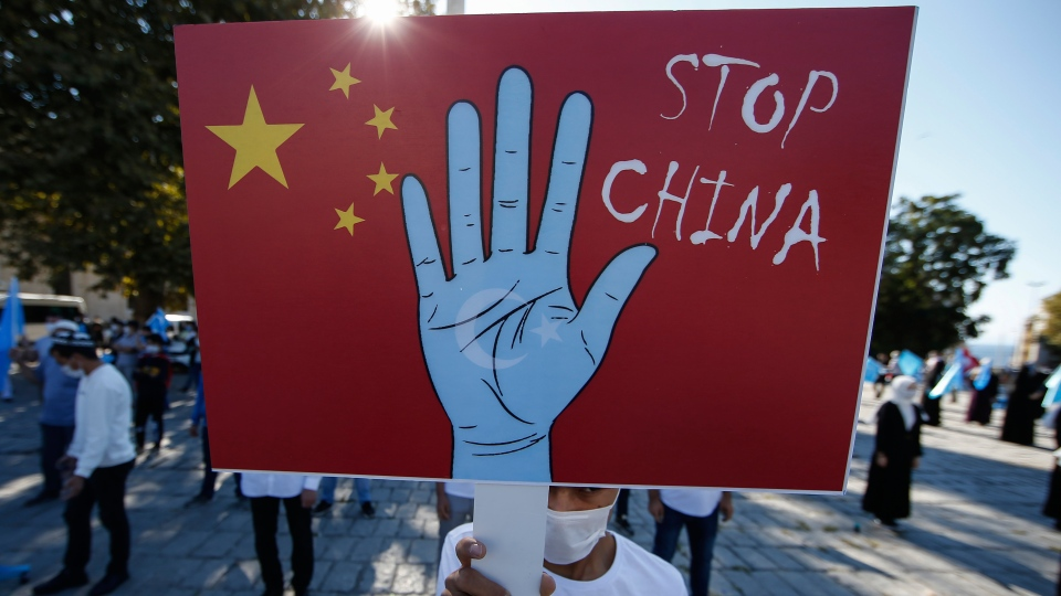 In this file photo taken Thursday, Oct. 1, 2020, a protester from the Uighur community living in Turkey, holds an anti-China placard during a protest in Istanbul, against what they allege is oppression by the Chinese government to Muslim Uighurs in far-western Xinjiang province. (AP Photo/Emrah Gurel, File)