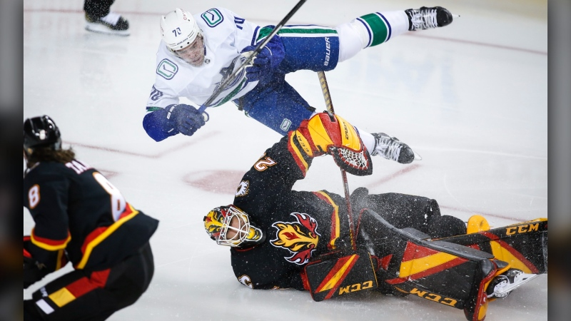 Vancouver Canucks' Tanner Pearson crashes over Calgary Flames goalie Jacob Markstrom during second period NHL hockey action in Calgary, Wednesday, Feb. 17, 2021.THE CANADIAN PRESS/Jeff McIntosh