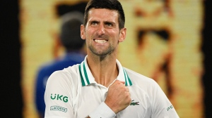 Serbia's Novak Djokovic celebrates after defeating Russia's Aslan Karatsev in their semifinal match at the Australian Open tennis championship in Melbourne, Australia, Thursday, Feb. 18, 2021.(AP Photo/Andy Brownbill)