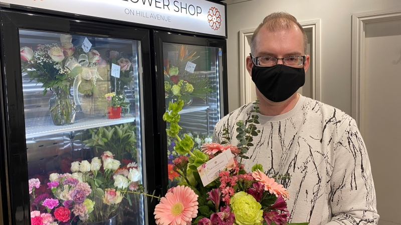 Kirk Leier, the owner of the Flower Shop on Hill Avenue, shows off a flower arrangement. (Gareth Dillistone/CTV News)